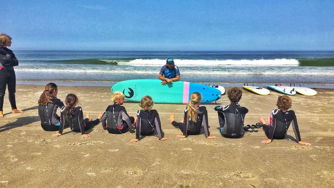Surfinstructeur met zijn leerlingen op het strand.